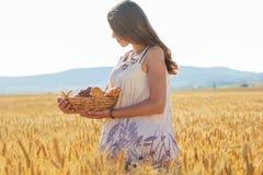 Muchacha en campo del centeno con la cesta de bollos y de rollos Foto de archivo libre de regalías