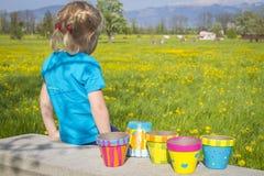 Muchacha en campo floreciente con los potes pintados coloridos del jardín Imágenes de archivo libres de regalías