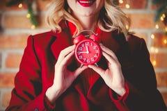 Muchacha en capa roja con el despertador imagen de archivo libre de regalías