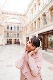 Muchacha en capa rosada que escucha la música con los auriculares afuera Imagenes de archivo