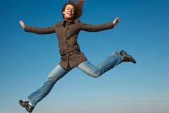 Muchacha en capa y pantalones vaqueros en salto contra el cielo azul Fotografía de archivo libre de regalías