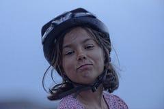 Muchacha en cara divertida del casco de la bici Imágenes de archivo libres de regalías