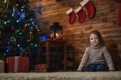 Muchacha en casa con un árbol de navidad, los presentes y las velas de celebra Imagen de archivo