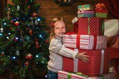 Muchacha en casa con un árbol de navidad, los presentes y las velas de celebra Fotografía de archivo