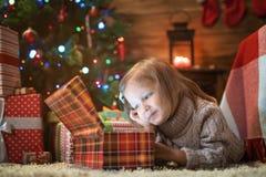 Muchacha en casa con un árbol de navidad, los presentes y las velas de celebra Imágenes de archivo libres de regalías