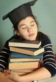 Muchacha en casquillo de la graduación con dormir de la pila del libro Foto de archivo