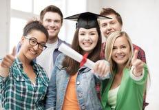 Muchacha en casquillo de la graduación con el diploma y los estudiantes Fotos de archivo libres de regalías