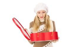 Muchacha en casquillo del invierno con un regalo aislado Imagenes de archivo