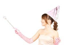 Muchacha en casquillo del partido con el palillo mágico Imagenes de archivo