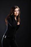 Muchacha en catsuit negro contra el fondo oscuro. Fotografía de archivo