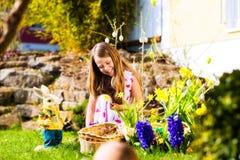 Muchacha en caza del huevo de Pascua con los huevos Fotos de archivo