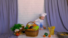Muchacha en cesta que cuida del sombrero del cocinero con las verduras frescas Concepto sano del alimento