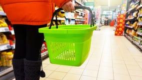 Muchacha en chaqueta anaranjada con la cesta que hace compras verde vacía que camina entre el estante en una tienda fotos de archivo
