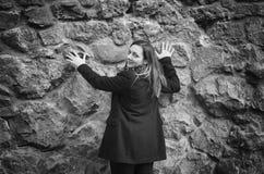 Muchacha en chaqueta con capucha afuera Muchacha en capilla y capa con equipaje cerca de la pared de piedra en la estación del ot imagen de archivo