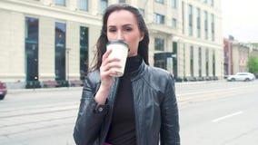 Muchacha en chaqueta, contra el fondo de la calle quita las gafas de sol, bebe el café almacen de video