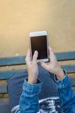 Muchacha en chaqueta de los vaqueros usando el teléfono elegante Foto de archivo