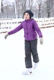 Muchacha en chaqueta del amanecer que patina en la pista de hielo Fotos de archivo libres de regalías