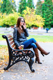 Muchacha en chaqueta que habla en el teléfono, sentando un banco, sosteniendo el café o el té, jóvenes al aire libre, caída de la Fotos de archivo libres de regalías