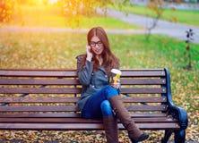 Muchacha en chaqueta que habla en el teléfono, sentando un banco, sosteniendo el café o el té, jóvenes al aire libre, caída de la Foto de archivo