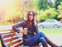 Muchacha en chaqueta que habla en el teléfono, sentando un banco, sosteniendo el café o el té, jóvenes al aire libre, caída de la Fotos de archivo