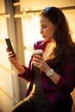 Muchacha en ciudad con smartphone y café para llevar Fotos de archivo libres de regalías