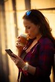 Muchacha en ciudad con smartphone y café para llevar Imagenes de archivo