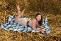 Muchacha en comida campestre en campo de trigo con la manzana Fotografía de archivo