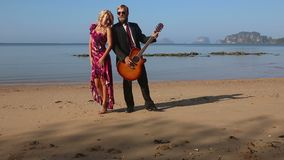 Muchacha en corchetes del rojo al pecho de los guitarristas en la playa en el amanecer almacen de video