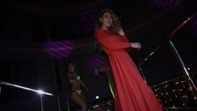 Muchacha en danza roja del vestido en soporte en partido en club nocturno Pelo de la sacudida Go va las muchachas almacen de metraje de vídeo