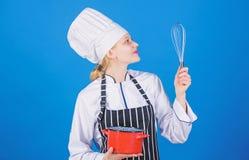 Muchacha en delantal que azota los huevos o la crema Comience lentamente a batir la crema que azota o de derrota Extremidades y t imagen de archivo