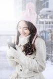 Muchacha en el abrigo de invierno que envía el mensaje con el teléfono móvil Imagen de archivo libre de regalías