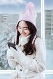 Muchacha en el abrigo de invierno que manda un SMS con smartphone Fotos de archivo libres de regalías