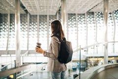 Muchacha en el aeropuerto de la parte posterior, con la taza de caf? imagenes de archivo