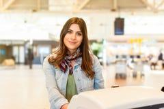 Muchacha en el aeropuerto usando la máquina del incorporar del servicio del uno mismo fotografía de archivo