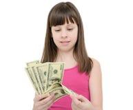 Muchacha en el asombro que sostiene el dinero en el fondo blanco Imagen de archivo libre de regalías