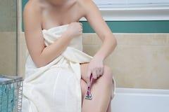 Muchacha en el baño que afeita sus piernas Fotografía de archivo