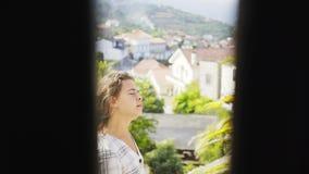 Muchacha en el balcón del chalet entre las colinas almacen de video
