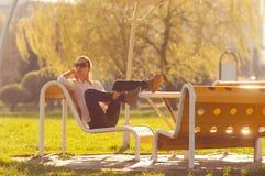 Muchacha en el banco en el parque Fotografía de archivo