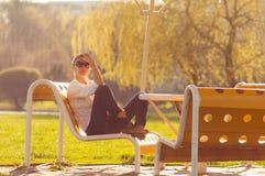 Muchacha en el banco en el parque fotos de archivo libres de regalías