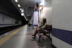Muchacha en el banco en la plataforma del subterráneo Foto de archivo libre de regalías