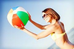 Muchacha en el bikini que juega la bola en la playa Fotografía de archivo