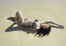 Muchacha en el bikini que miente en una playa arenosa Imagen de archivo