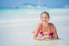 Muchacha en el bikini que miente y que se divierte en la playa tropical Imagen de archivo libre de regalías