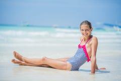 Muchacha en el bikini que miente y que se divierte en la playa tropical Fotografía de archivo