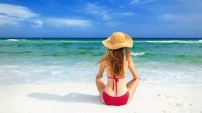 Muchacha en el bikini rojo que se sienta en la playa blanca de la arena Fotos de archivo libres de regalías