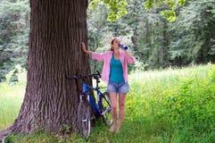 Muchacha en el bosque con un agua potable de la bicicleta Fotos de archivo libres de regalías
