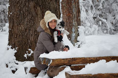 Muchacha en el bosque del invierno con su perro Foto de archivo