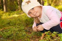Muchacha en el bosque, recogiendo bayas Foto de archivo libre de regalías