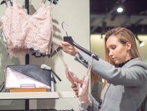 Muchacha en el boutique para elegir la ropa en venta fotos de archivo libres de regalías