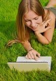 Muchacha en el césped que trabaja en la computadora portátil Imagen de archivo libre de regalías